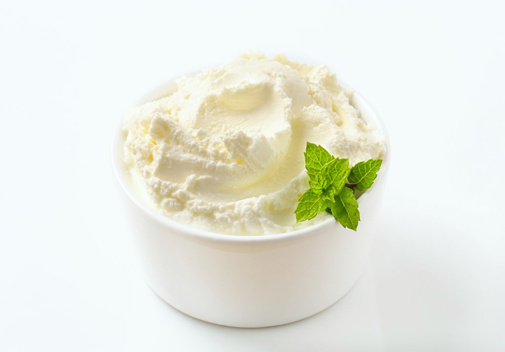 Sweet soft cream cheese with mint in a small white bowl