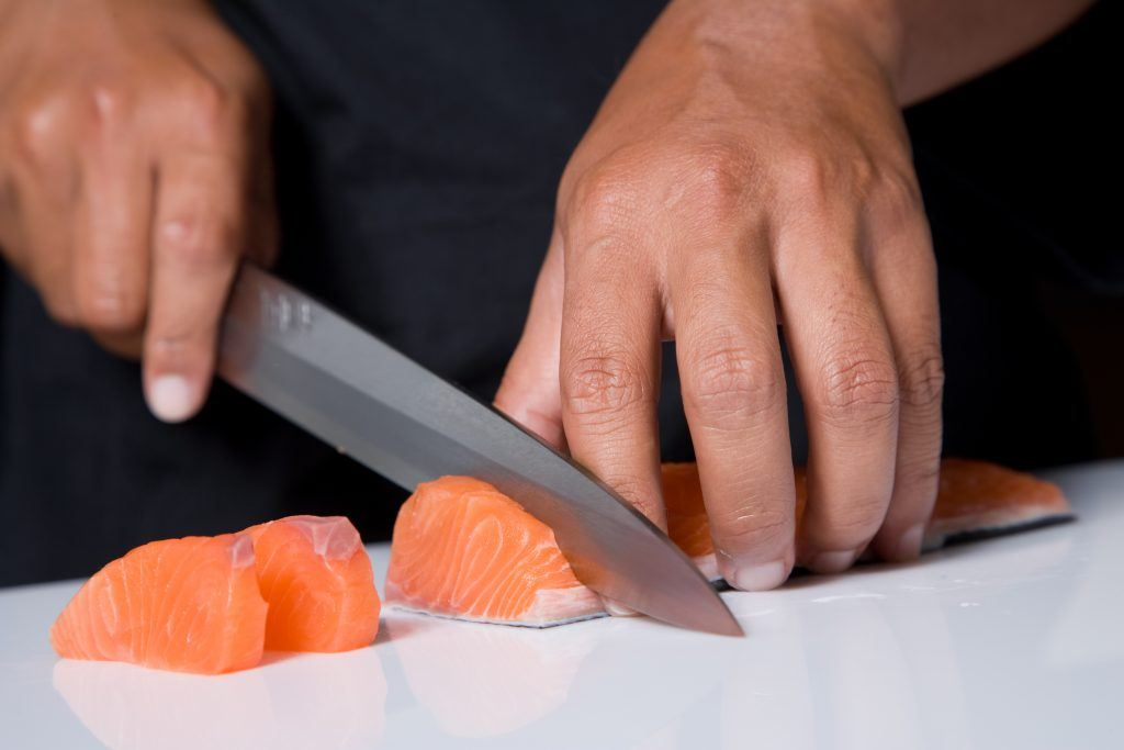 A Japanese Chef Cutting Raw Fish For Sushi