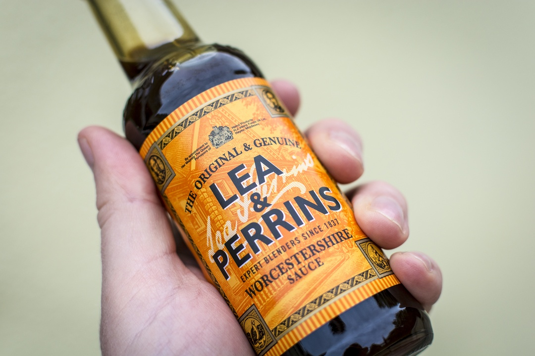 Close up of a male hand holding a bottle of Lea & Perrins Worcestershire Sauce - a popular condiment / cooking ingredient.